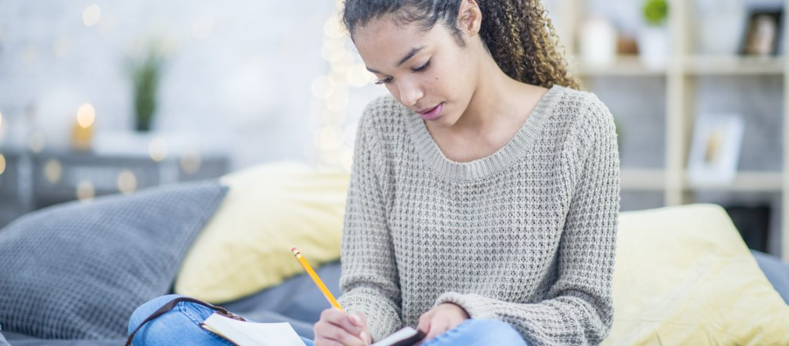 A pretty teenaged girl writes into a journal with interest while sitting cross legged on her bed.