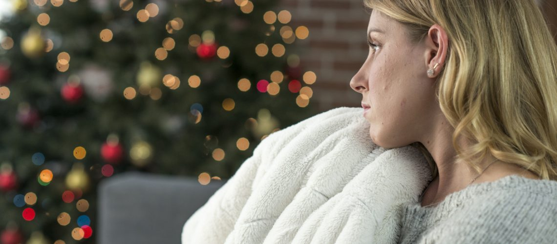 A woman is having a lonely Christmas by herself. She sits alone and looks sad as she is all alone on Christmas. Here she sits with a blanket while looking depressed.